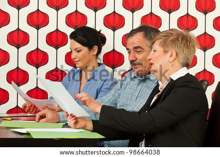 Group of three executives having conversation and working in modern office - stock photo