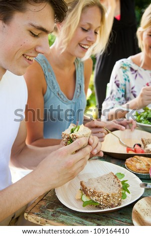 Group of three friends having an outdoors picnic in the summer garden