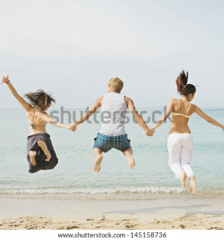 Group of three friends holding hands and jumping at once on the shore of a golden sand beach against a blue sea and sky, expressing energy, fun and joy.