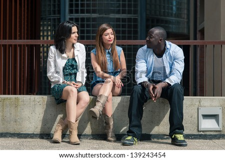 Group of three friends talking together outdoors on a bench. - stock photo