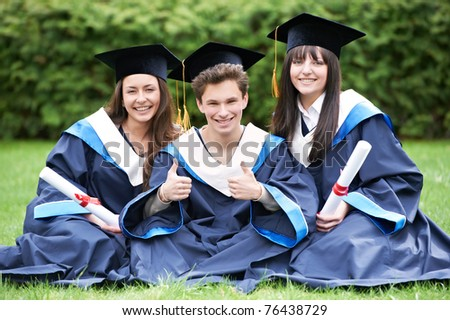 group of three graduate students sitting in the park cheerful and happy - stock photo