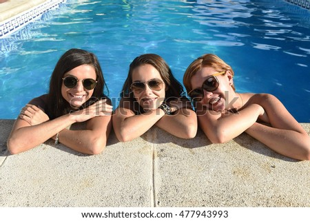 group of three happy beautiful young girl friends having bath in swimming pool together having fun enjoying summer at vacation resort smiling in women holiday concept
