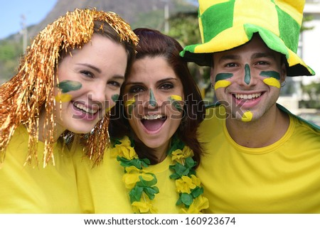 Group of three happy Brazilian soccer fans commemorating victory.
