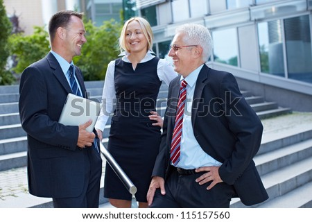 Group of three happy business people discussing a deal outside - stock photo