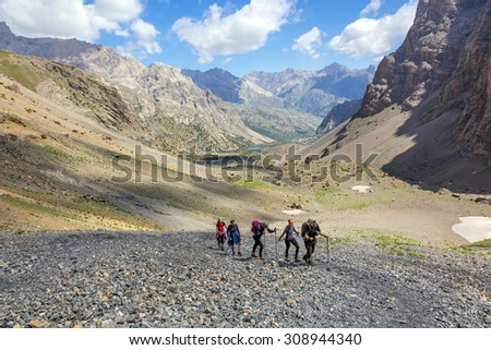 Group of three hikers on trail. Mountain landscape and people walking with poles backpacks and other gear along dusty Asian trail with green grass and orange rocks around - stock photo