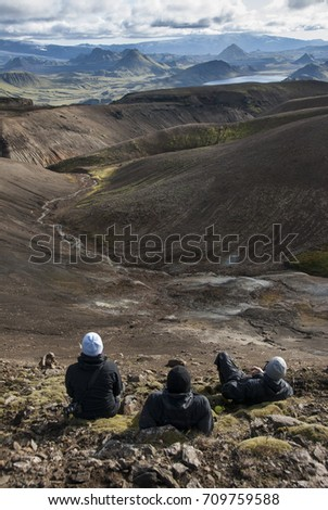 Group of three hikers taking a rest while enjoying beautiful mountains on Iceland