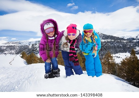 Group of three kids, girls hugging together standing on hiking trail
