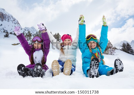 Group of three kids girls sitting in snow together holding hands - stock photo