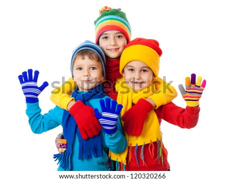 Group of three kids in bright winter clothes, isolated on white
