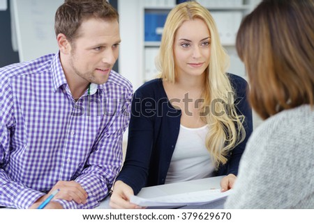 Group of three male and female cheerful young adult workers discussing notes in office during meeting - stock photo