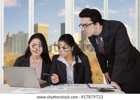 Group of three multi ethnic businesspeople meeting in the office with laptop computer on desk