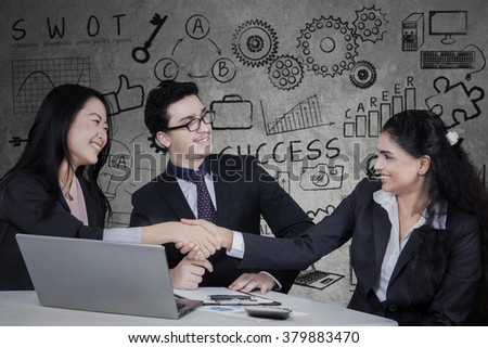 Group of three multiracial businesspeople closing a deal by shaking hands, shot with business doodles background - stock photo