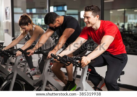 Group of three people enjoying their spinning session at the gym and smiling - stock photo