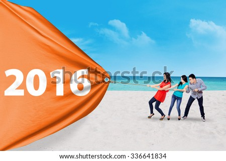 Group of three people pulling an orange banner with numbers 2016 on the beach - stock photo
