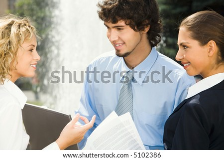 Group of three people talking  about their business examination