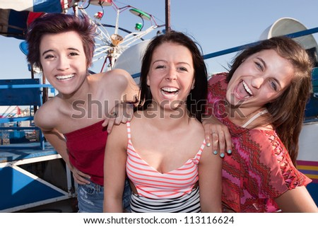 Group of three pretty teenage girlfriends at an amusement park - stock photo