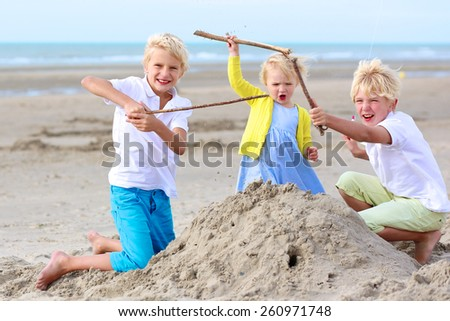 Group of three smiling children, preschooler girl and teenage boys playing together on the beach building sand castles on sunny summer day - stock photo