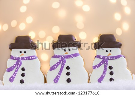 Group of three snowmen cookies in snow with lights - stock photo