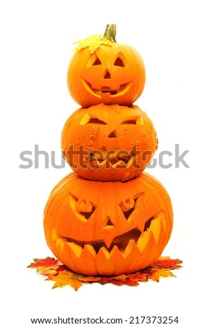 Group of three stacked Jack o Lanterns with autumn leaves - stock photo