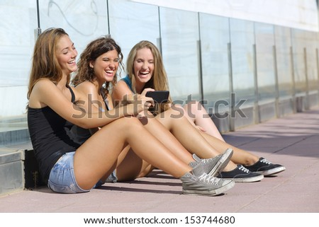 Group of three teenager girls sitting on the floor laughing while watching the smart phone - stock photo