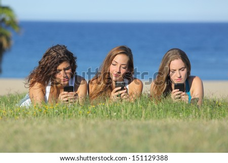 Group of three teenager girls typing on the mobile phone lying on the grass with the sea in the background - stock photo