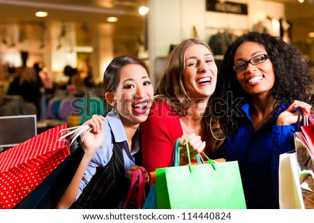 Group of three women - Caucasian, Latina and Asian - shopping downtown in a mall - stock photo