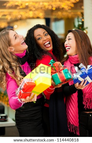 Group of three women - white, black and Asian - with Christmas presents in a shopping mall in front of a Christmas tree - stock photo
