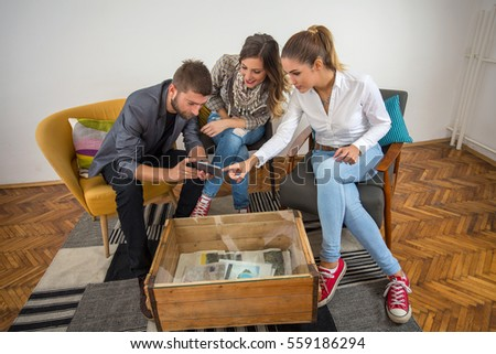 Group of three young business people using mobile phone while having a meeting or coffee break in their modern office