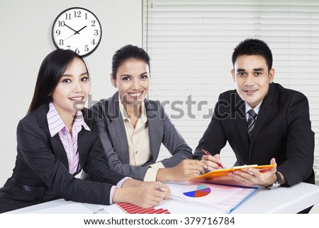 Group of three young businesspeople in a business meeting, sitting in the office and smiling at the camera - stock photo