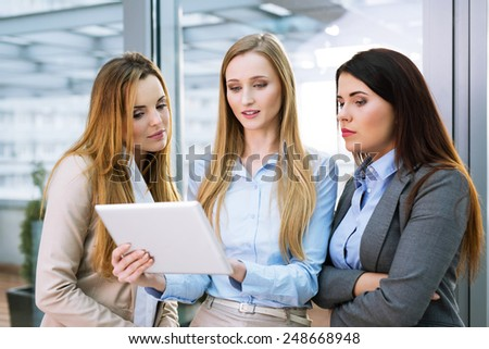 Group of three young female entrepreneurs looking at a digital tablet and talking - stock photo