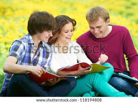 Group of three young students studying with note books in spring outdoors - stock photo