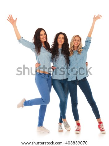 group of three young women celebrating success on white background, with hands in the air