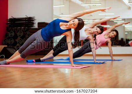 Group of three young women practicing the side plank pose during yoga class in a gym - stock photo