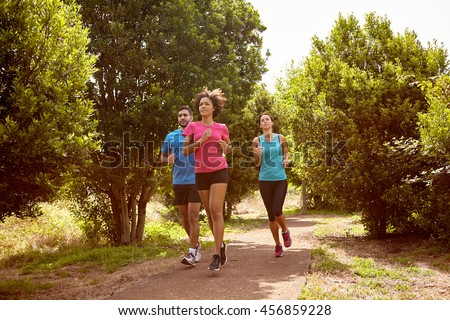 Group of three youngsters running through a natural trail in daylight surrounded by trees and bushes in the late morning wearing t-shirts and black pants - stock photo