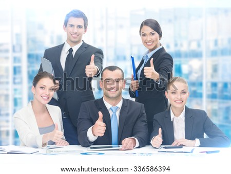 Group of thumbing up business people working at the table, blue background. Concept of teamwork and cooperation - stock photo