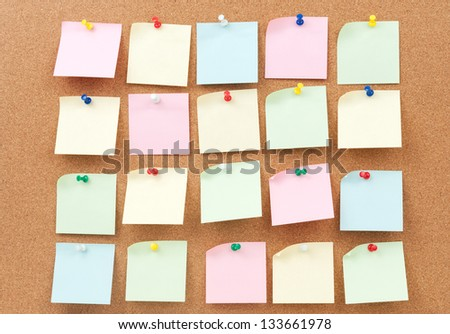 Group of thumbtack and note paper on cork board - stock photo