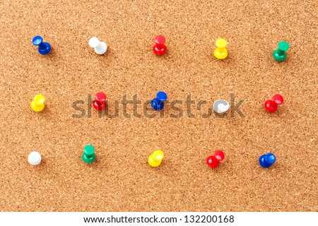 Group of thumbtacks pinned on corkboard - stock photo