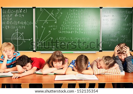 Group of tired school children at a classroom. Education. - stock photo