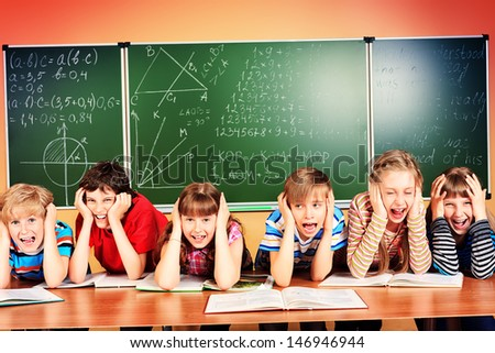 Group of tired school children at a classroom grabing their heads. Education. - stock photo