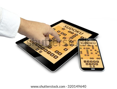group of touchscreen devices with sudoku game and a hand touching the screen isolated on white background - stock photo