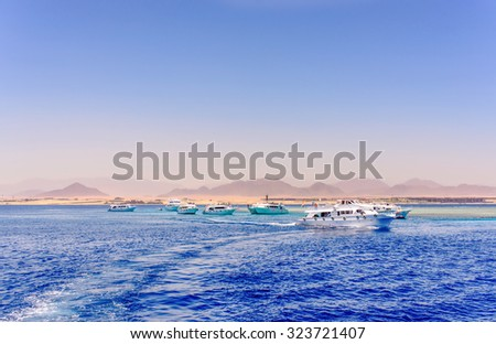 Group of tour ships and dive boats moored off an offshore reef and sand bar in a calm blue tropical ocean on a hot summer day