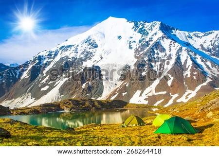 Group of tourists in the camp on the shore of a quiet lake, on the back of high snowy mountains on a clear, sunny day with beautiful clouds.