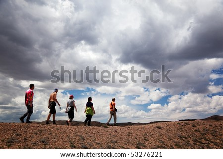 Group of tourists in the desert and storm clouds - stock photo