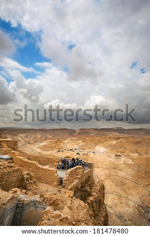 Group of tourists on a viewing point  of the ancient Masada fortress in Israel - stock photo