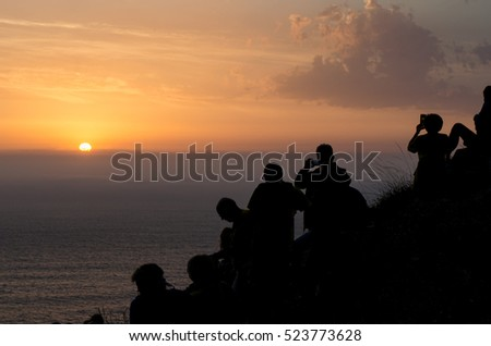 Group of tourists photographing the sunset from Finisterre lighthouse, Galicia, Spain.