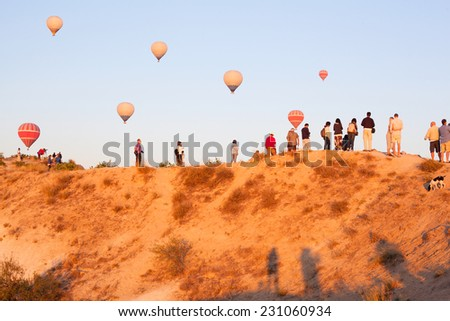 Group of tourists watching balloon fly on top of mountain, making photos in sunrise time, in Cappadocia, Turkey - stock photo