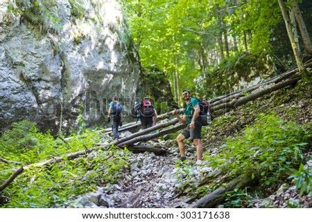 Group of tourists with backpacks going uphill on a steep trail in the mountains - stock photo