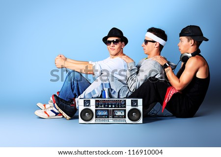 Group of trendy teenagers posing with boombox at studio. - stock photo