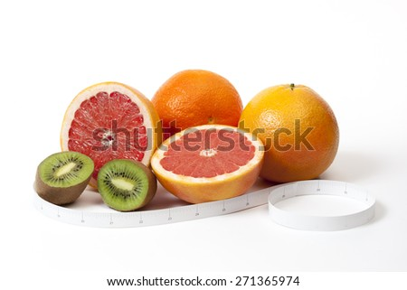 Group of tropical fruits and tape measure in inches around, shooted over white - stock photo