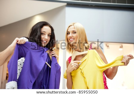 Group of two beautiful shopping women trying on clothes at shopping mall indoors - stock photo